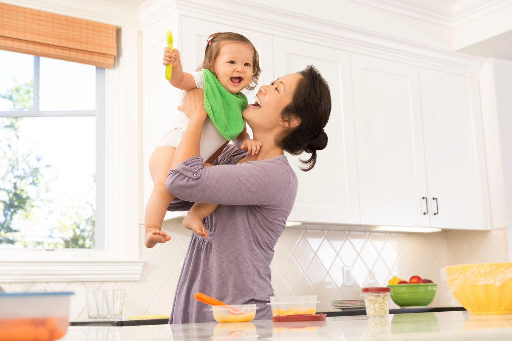 woman in a kitchen holding her toddler with food on the counter in front
