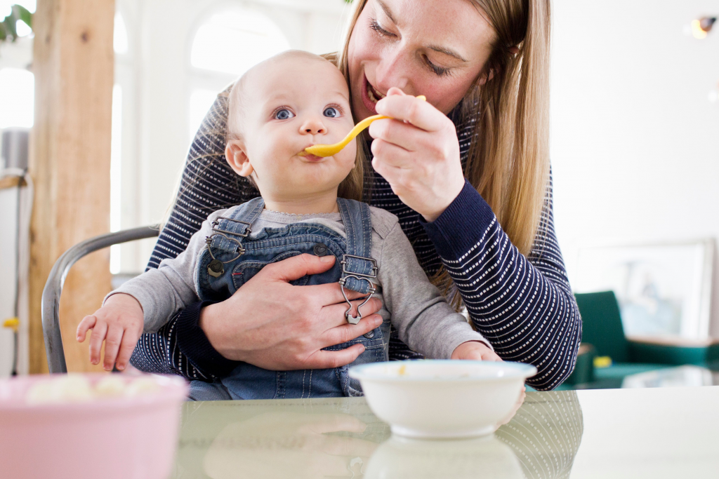 woman holding and spoon feeding her baby on her lap